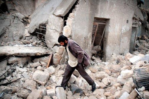 Syrian man walks amid debris