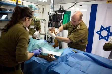 Israeli medics treat a wounded Syrian man at a field hospital