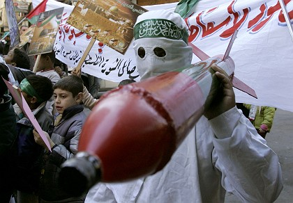A Hamas supporter carries a mock Qassam rocket